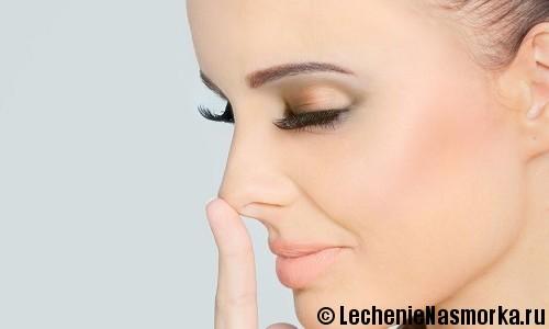 девушка дотрагивается кончиком пальца носа